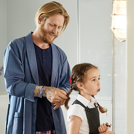 Dad plaiting his daughter's hair