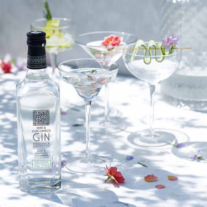 Mint and cucumber gin in cocktail glasses with flower garnish