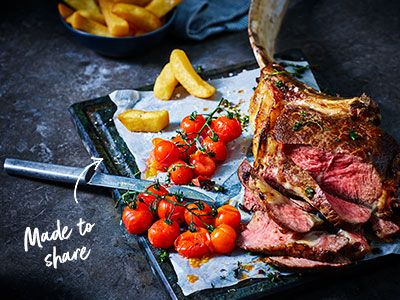 Sliced tomahawk steak with roasted cherry tomatoes and triple-cooked chips