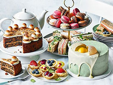An Easter afternoon tea spread with sandwiches, simnel cake, fruit tarts, macaroons and our cracked egg cake