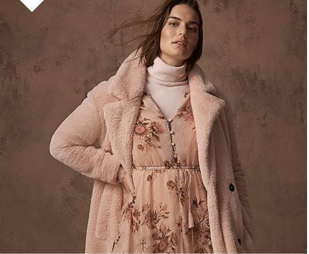 Model wears a pink shearling coat over a pink floral-print midi dress and pink roll-neck jumper