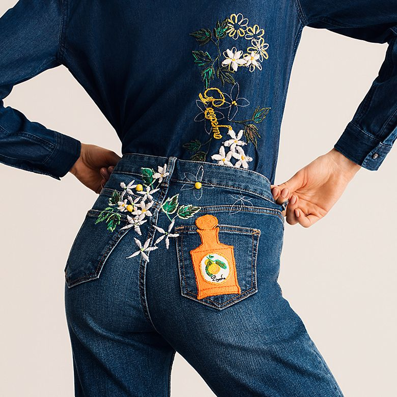 Woman wearing jeans with floral and a bottle of Monotheme perfume embroidery