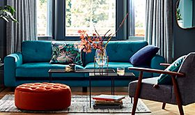 Blue sofa and orange footstool in room