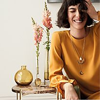 Laughing woman wearing a yellow top and statement necklaces, leaning on a marble table decorated with vases of flowers