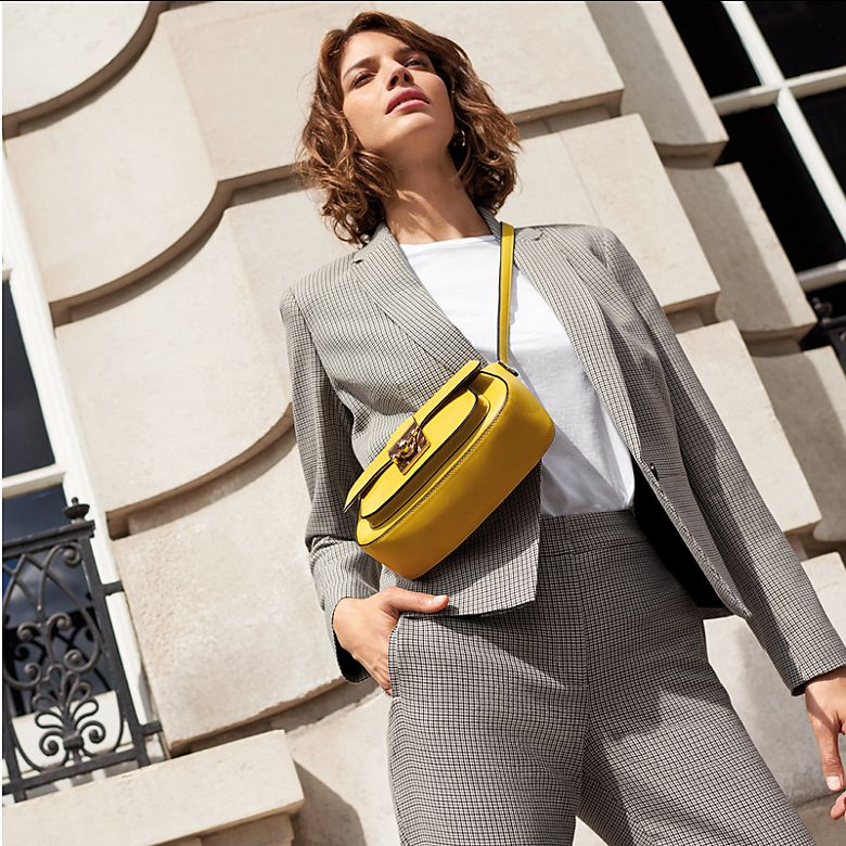 Woman wearing light grey trouser suit with yellow bag