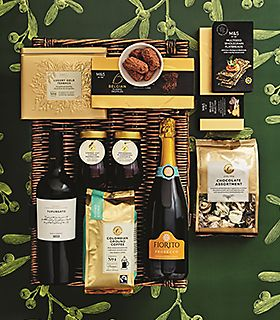 Wicker hamper surrounded by wine and condiments
