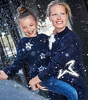 Woman and girl in the snow wear matching Christmas jumpers