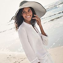Woman walking on a sandy beach wearing a sun hat and white linen cover-up