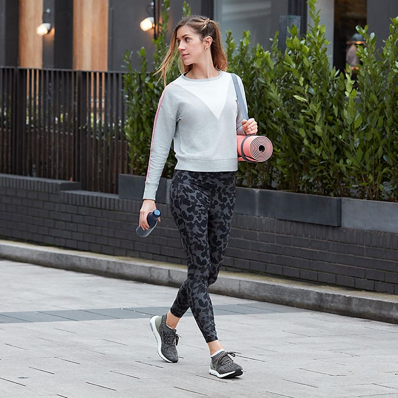 M&S fashion editor Sophie Hines carrying yoga mat in colour-block sweatshirt and animal-print leggings
