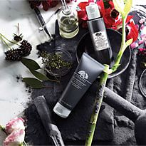 Origins Clear Improvement range surrounded by charcoal and flowers
