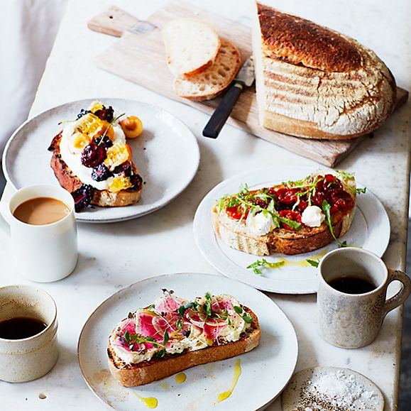 A loaf of sourdough with different toppings and coffee