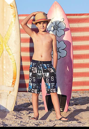 Boy in long printed trunks with a surfboard on the beach