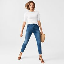 Woman wearing a white top, blue jeans, tan sandals and a straw bag