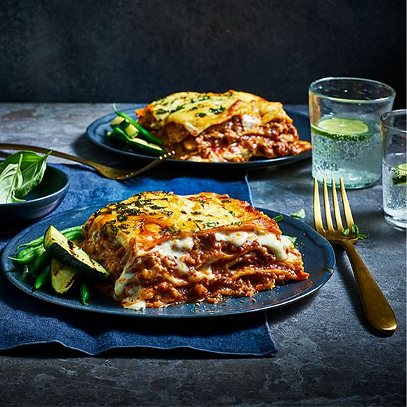 Two plates of delicious lasagne on a table
