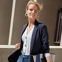 Woman wearing a navy blazer, white shirt and blue jeans