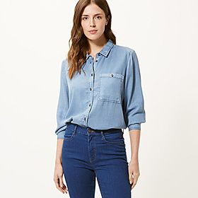 Woman wearing a blue denim shirt and blue jeans