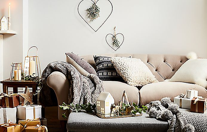 Living room with a sofa, cushions, throws and Christmas decorations