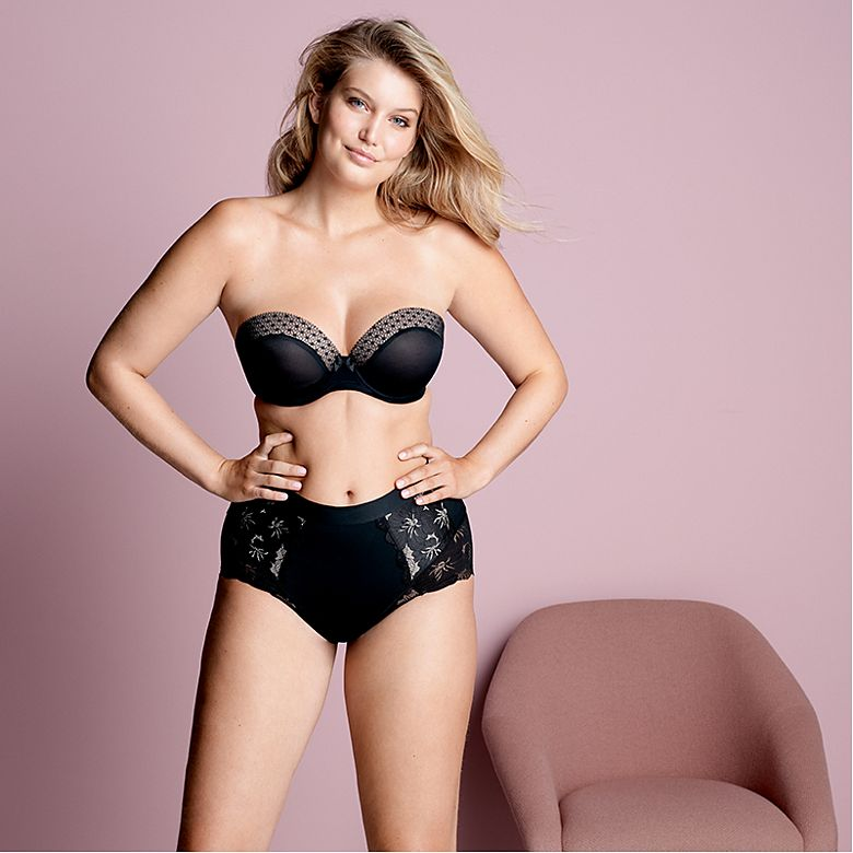 Woman wears black strapless bra and shapewear briefs