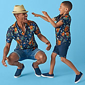 Man and child wearing octopus-print shirts and denim shorts