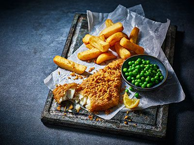 Beer-battered cod and scraps served with triple-cooked chips, peas and lemon