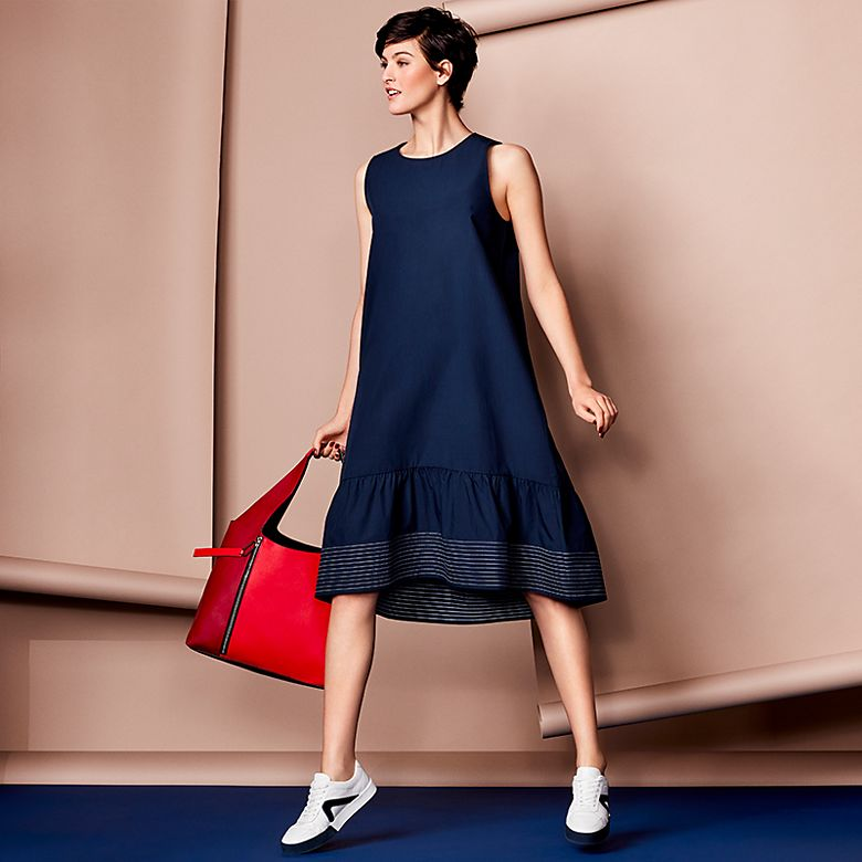 Model wears blue shift dress and red bag