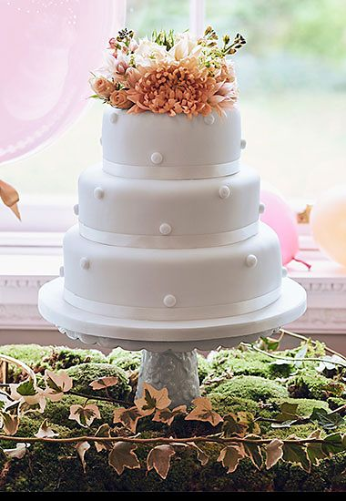 White wedding cake topped with pink flowers