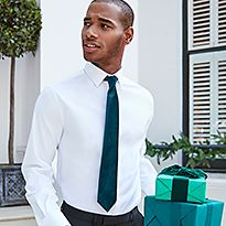 Man wearing a white shirt and black tie carries Christmas gifts