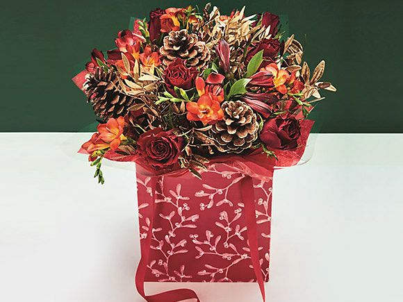 Red gift bag with a festive flower bouquet
