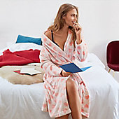 Woman sat on a bed wears a heart-print dressing gown