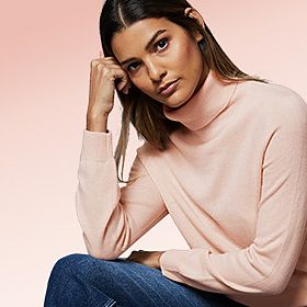 Woman wearing pale pink roll-neck cashmere jumper