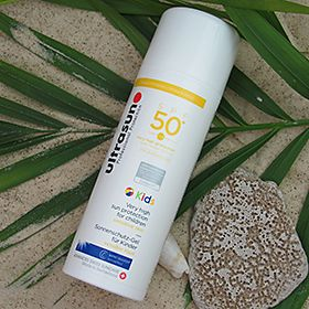 Ultrasun sun cream on a beach next to shells