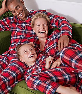 Family on a sofa wear matching Christmas pyjamas