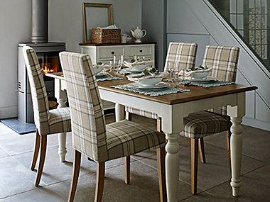 Dining table surrounded by tartan-print chairs