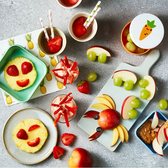 A selection of child-friendly snacks including pineapple emojis and fruity water