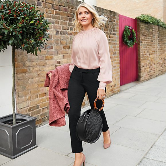 Holly Willoughby wears a pink blouse, black trousers, pink court shoes and a black basket-weave bag