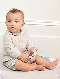 Baby in M&S clothes playing with a toy