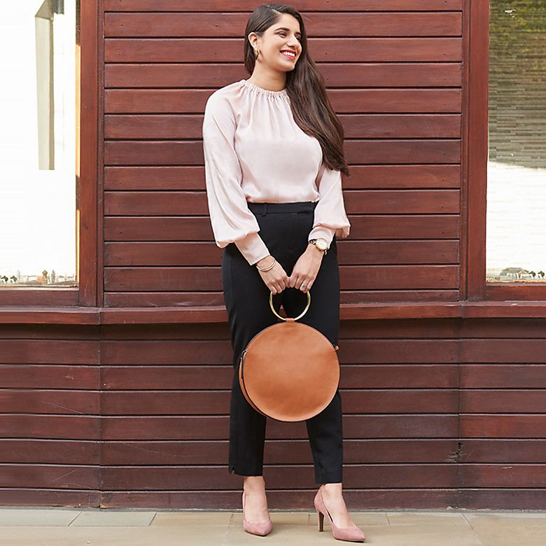 Ravina wears blush pink blouse and black trousers from Holly's Must-Haves collection