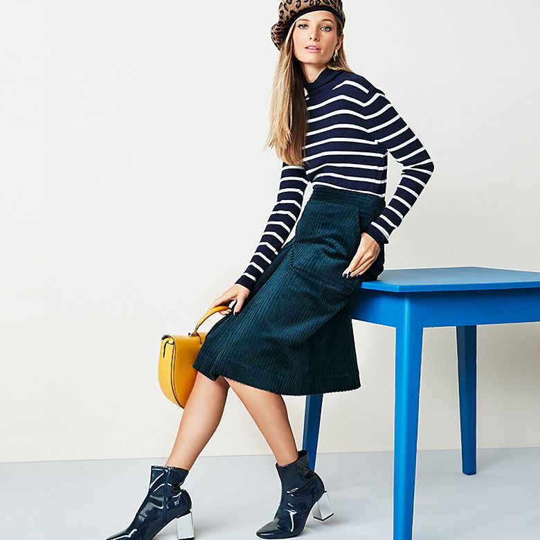 Model wears striped roll neck and cord skirt