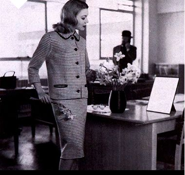 Woman wearing coordinated printed skirt suit in the office, 1959