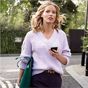 Woman wearing a lilac jumper with cable-knit sleeves