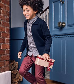 Boy walking out of a front door holding a Christmas gift