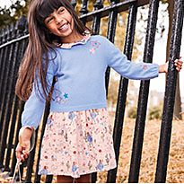 Girl wearing a pink floral print dress with a blue jumper