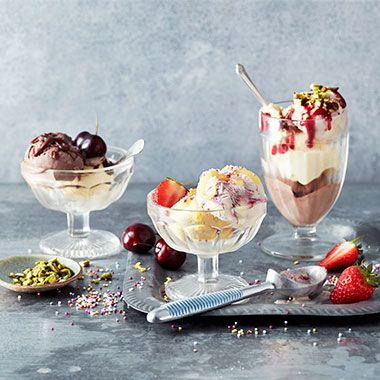 A trio of ice cream sundaes with fresh fruit and chopped nuts