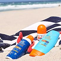 Various sunscreens and sun tan lotions on a beach