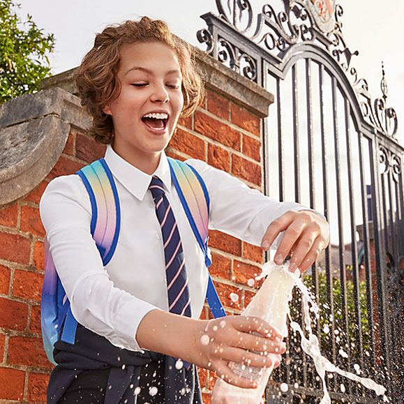 Child wearing M&S school uniform opening a bottle of sparkling water