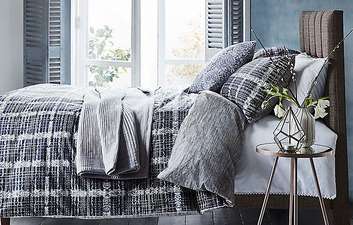 Ikat-print bedding set on a divan bed e8572f49d