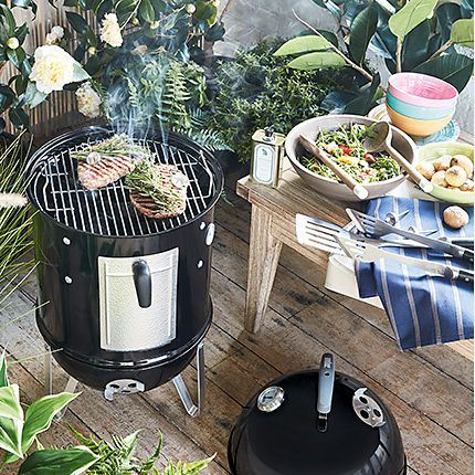 Barbecue and table with barbecue food