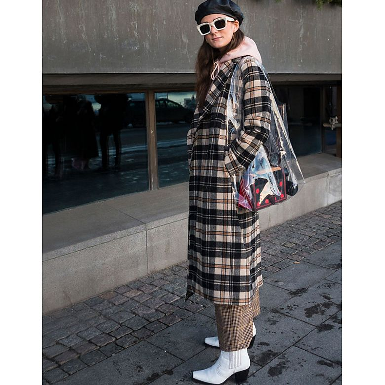 Woman wears checked coat with hoodie and white cowboy boots