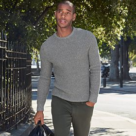 Man wearing tapered-fit jeans and a grey jumper