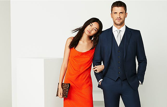Woman wearing a red slip dress and a man wearing a navy three-piece suit